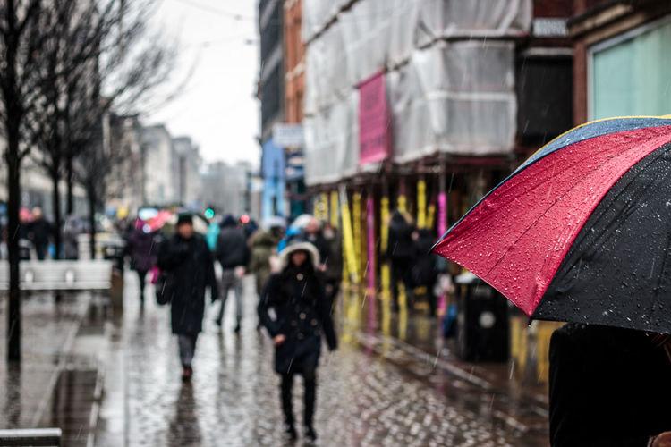People Walking On City Street On Rainy Day