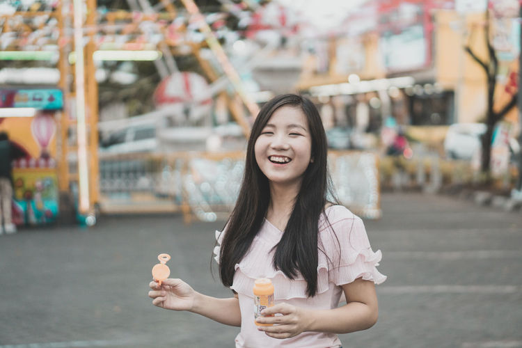Portrait of smiling young woman holding bubble wand at amusement park