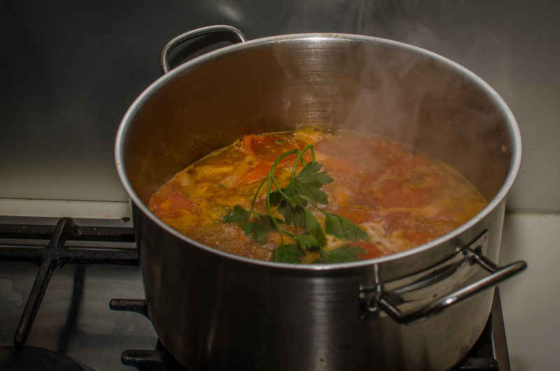 Close-Up Of Tomato Soup Cooking In Saucepan On Gas Stove Burner