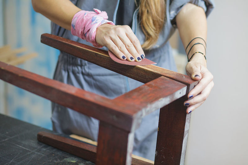 Midsection of woman working on wooden table