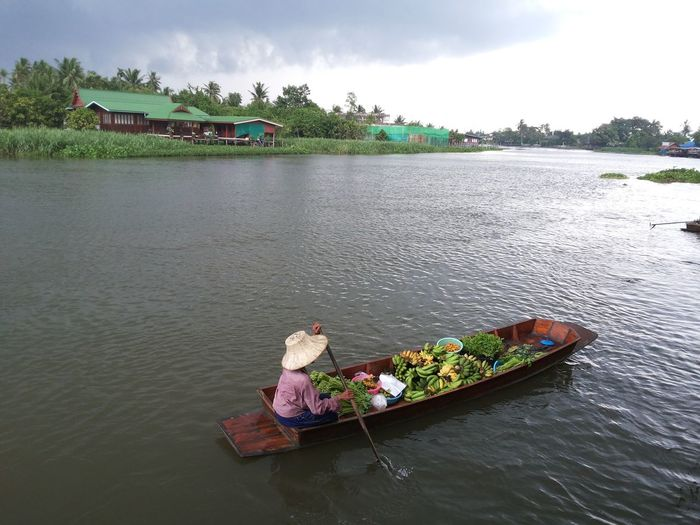 High angle view of woman sitting on lake against sky