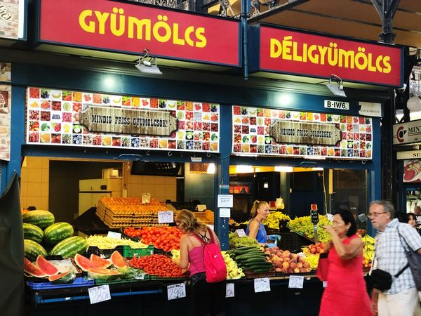 A green grocer stall in a market in Budapest, Hungary. Shop Vegetable Fruit Stall Market Budapest Text Western Script Communication Business Food And Drink Food Women Store Retail  Choice People Small Business