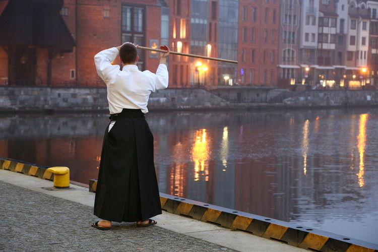 Rear view of man practicing martial arts while standing on bridge in city during sunset