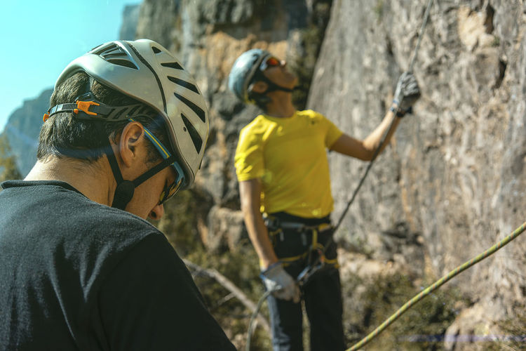 Two climbers belaying Headwear Men Helmet Lifestyles Two People Adventure Day Sport Climbing Rock People Sports Helmet Nature Safety Outdoors Mature Men Climbers Belay Belaying Climbing Course Course Training Activity