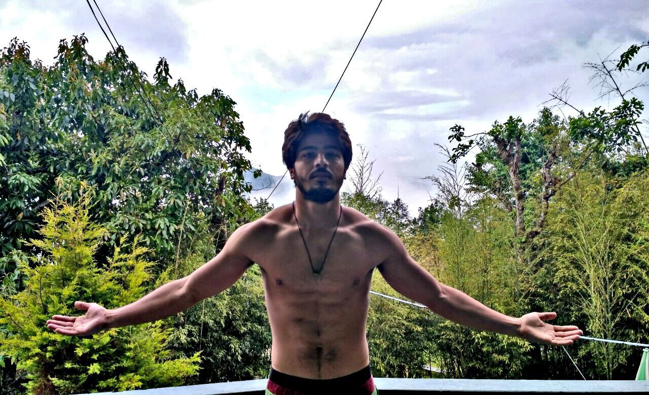 shirtless, tree, one person, real people, lifestyles, sky, cloud - sky, standing, muscular build, growth, day, leisure activity, young men, outdoors, men, healthy lifestyle, one man only, strength, young adult, low angle view, nature, one young man only, portrait, only men, sportsman, adult, people