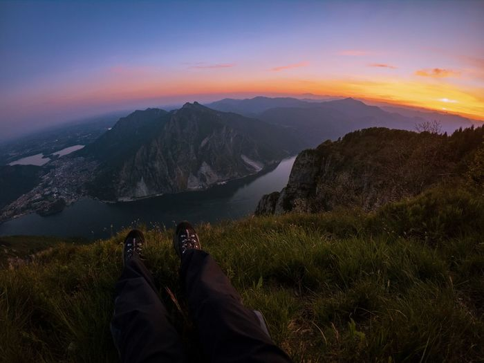 Low section of man sitting on mountain against sky during sunset