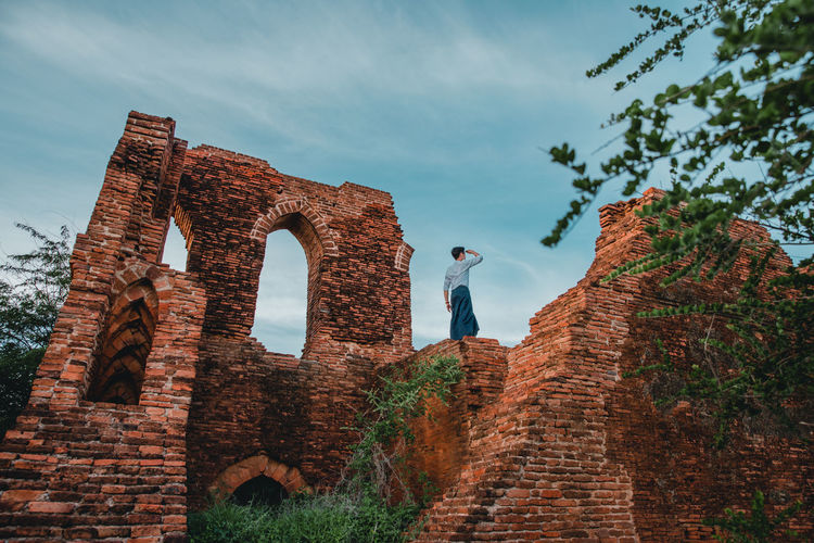 Low angle view of man standing on old ruins against sky