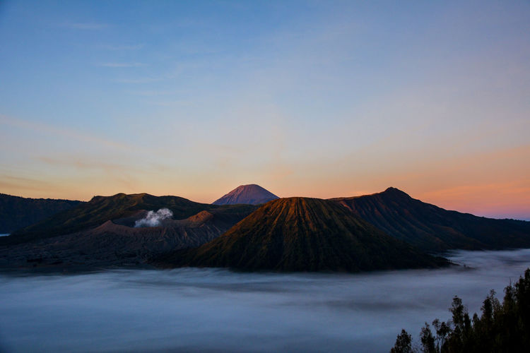 Scenic view of volcanic mountain against sky during sunset