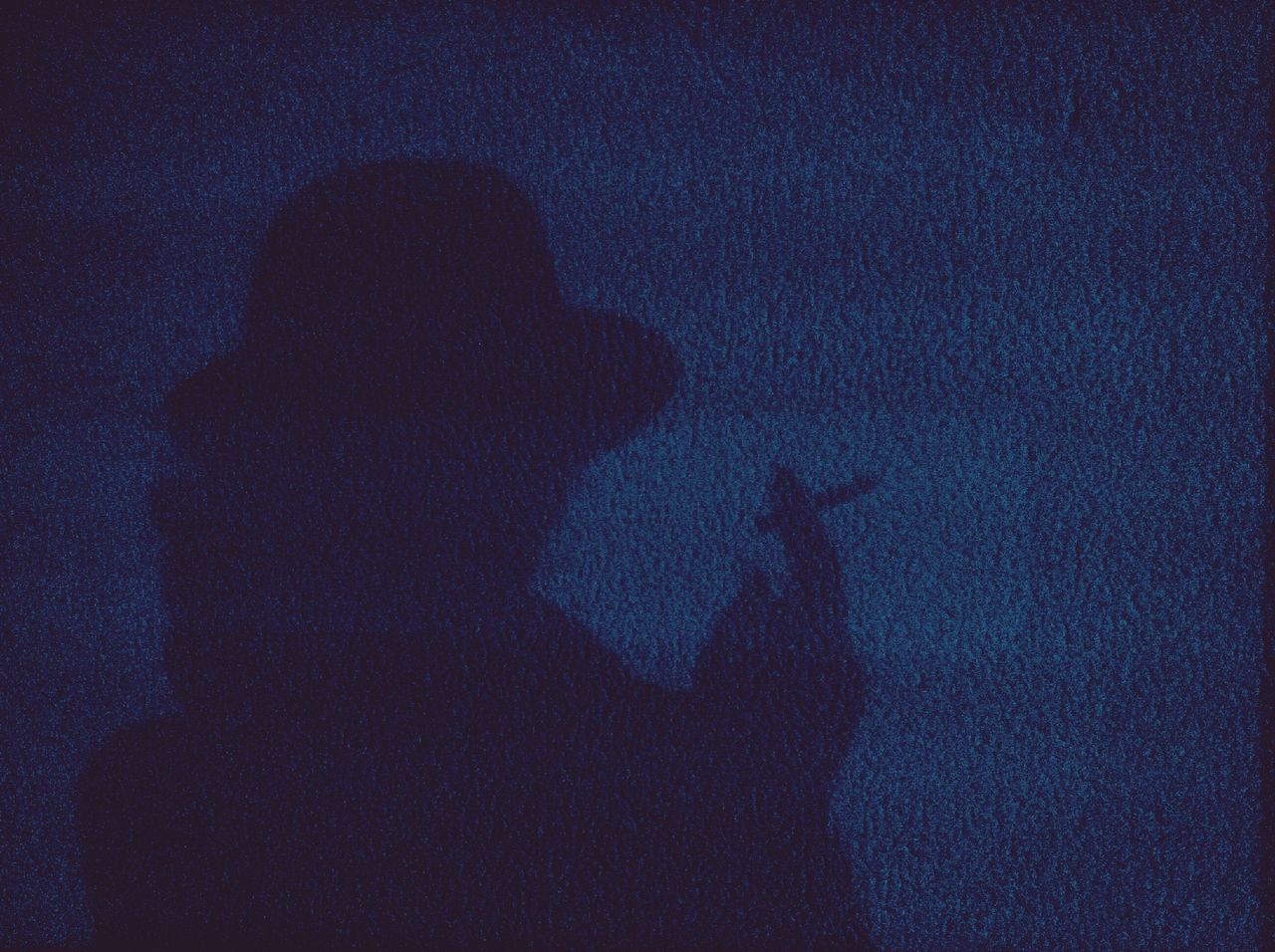 Shadow of a man with cigarette on the wall