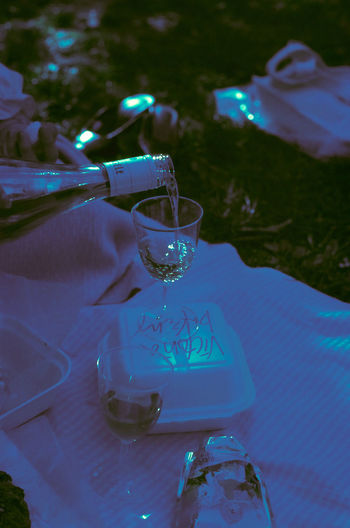 Close-up of hand pouring wine glass on table
