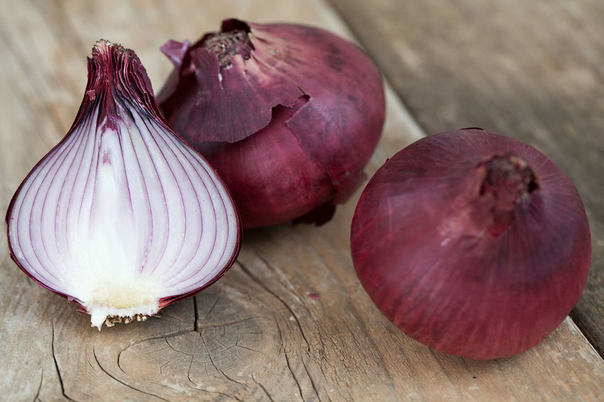 Whole and half red onions Cut Raw Vegetarian Food Bulb Close-up Food Food And Drink Fresh Freshness Half Healthy Eating Indoors  Ingredient No People Nutrition Onion Organic Purple Red Color Ripe Slices Still Life Table Vegetable Wood - Material