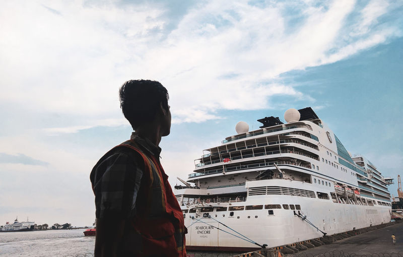 Low angle view of man standing by ship against sky