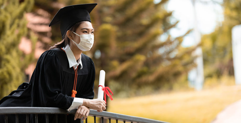 Woman in graduation gown holding certificate against trees