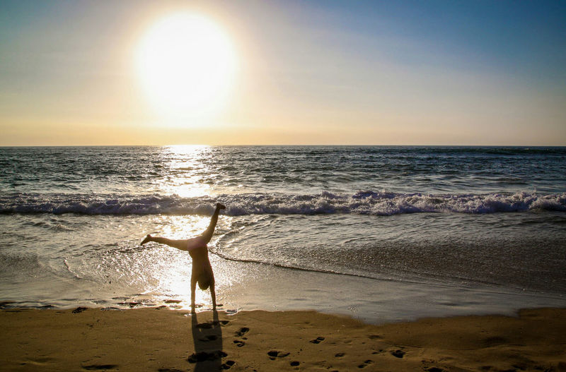 Rear view of woman practicing cartwheel on shore at beach against sky during sunset