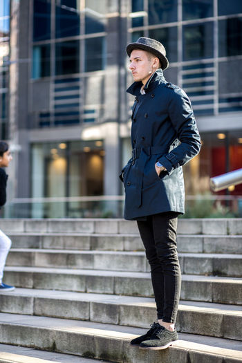 Man in smart, fashionable business wear standing outside in hat. Adult Adults Only Blue Business City Coat Corporate Day Fashion Fashion Photography Full Length Hat Long Coat Men One Man Only One Person Only Men Outdoors People Smart Stylish Young Adult