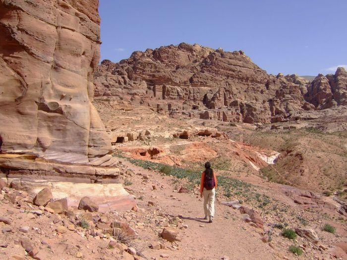 Rear view of woman walking in rocky landscape