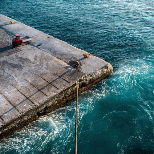 High angle view of rope tied on bollard by turquoise sea