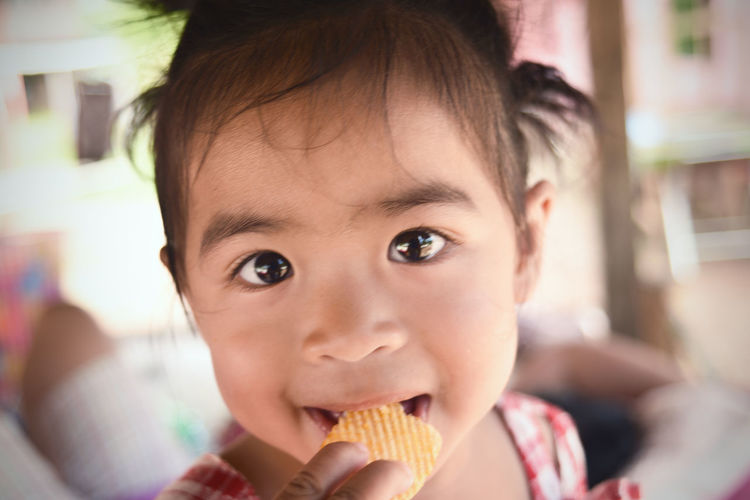 Close-up portrait of cute baby girl eating potato chips