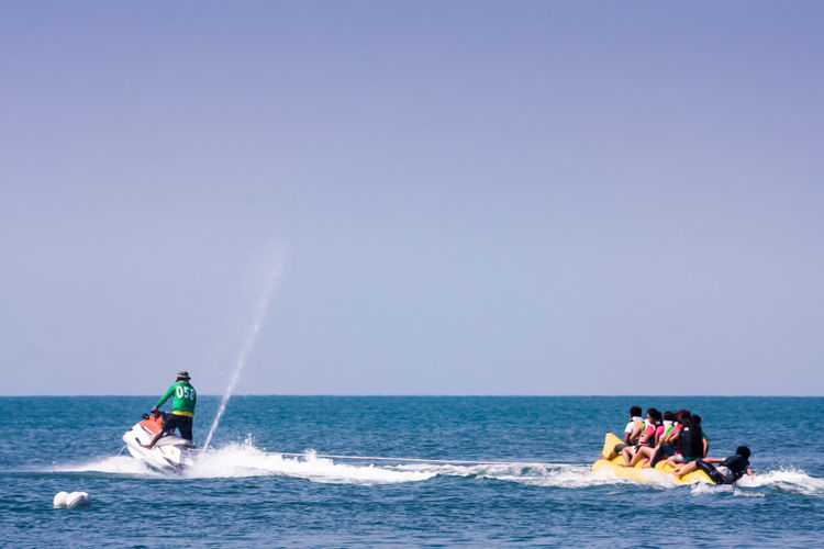 Rear view of man on jet boat pulling people on banana ride in sea
