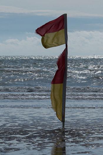 Flag on pole by sea against sky