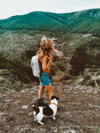 Girl and her dog walking the mountains