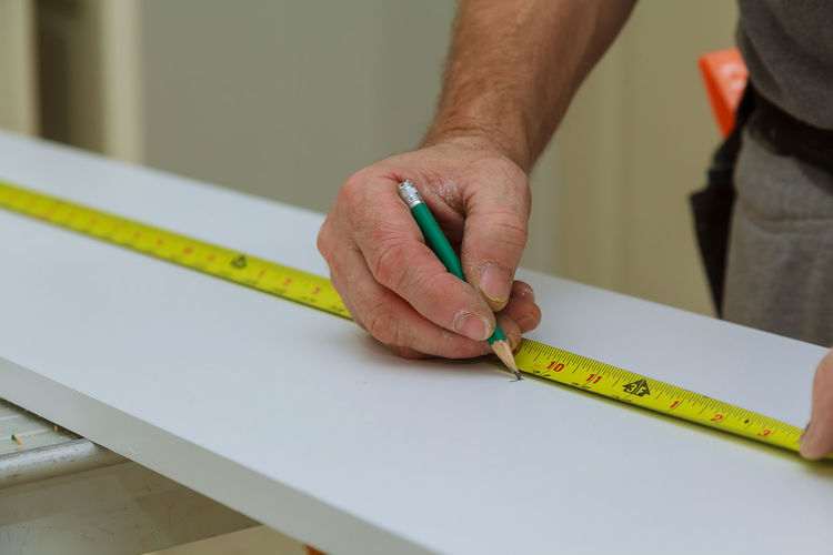 Midsection of man measuring wood in workshop
