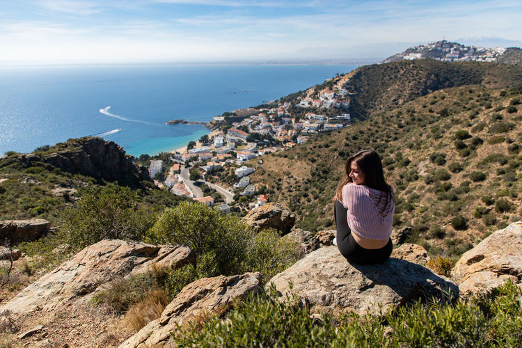Rear view of woman sitting on cliff against sea