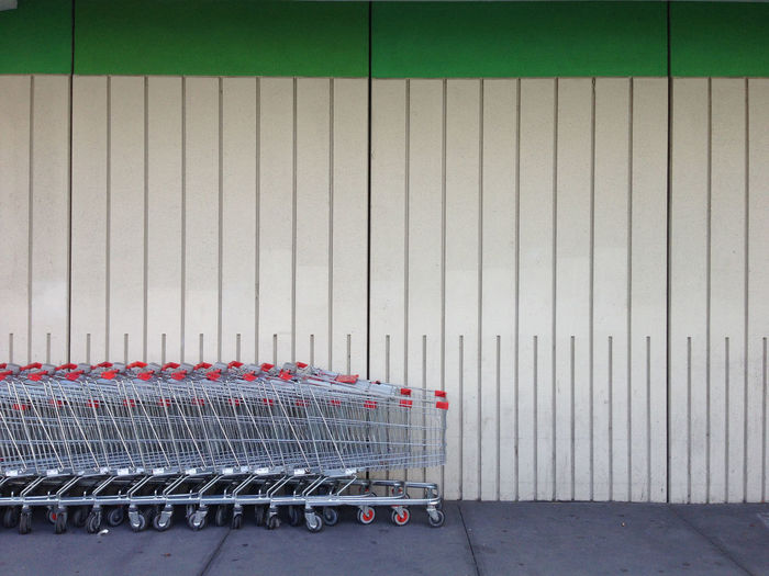 Row of shopping carts next to a wall