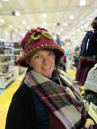 Portrait Of Smiling Woman Wearing Hat And Scarf At Store