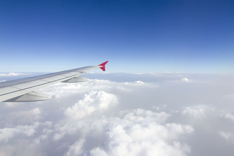 Airplane flying over cloudscape against sky