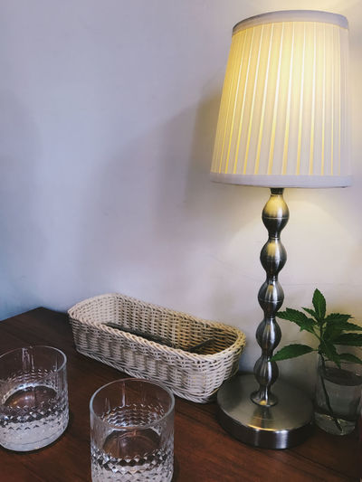 Close-up of illuminated lamp on table against wall at home
