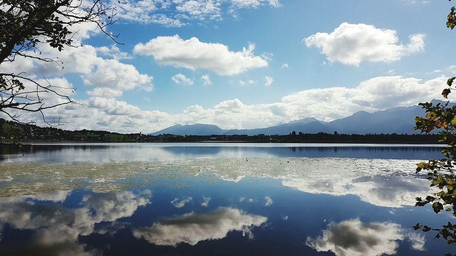 Scenic view of lake with reflection against cloudy sky