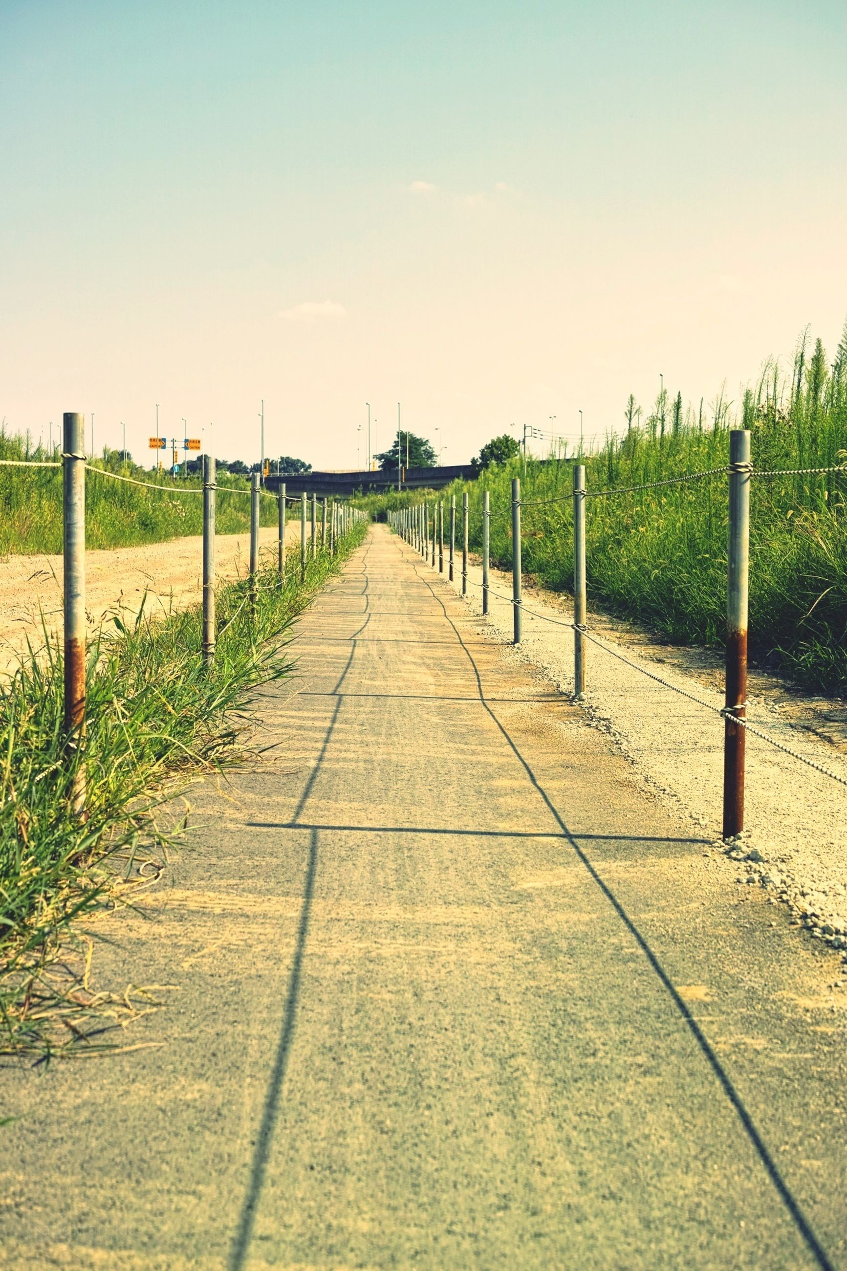 the way forward, diminishing perspective, vanishing point, tranquility, railing, tranquil scene, grass, sky, fence, clear sky, footpath, long, nature, walkway, pathway, empty, narrow, landscape, field, scenics