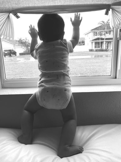Rear view of boy looking through window at home