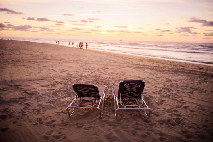 Empty Chairs At Beach During Sunset