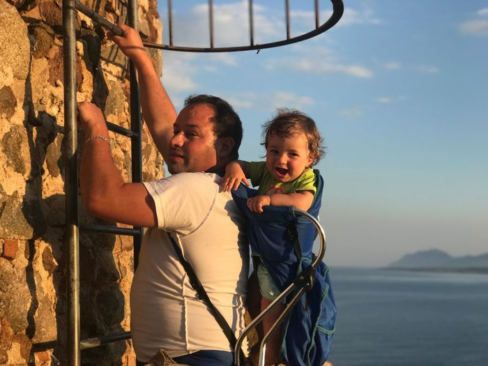 Father climbing ladder on wall while carrying son against sky