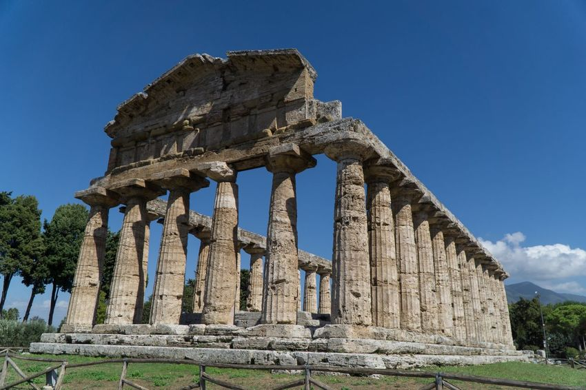 Paestum Roman ruins, Italy Roman Ruins History The Past Architecture Ancient Sky Built Structure Old Ruin Low Angle View Travel Archaeology Tourism Place Of Worship Ancient Civilization Travel Destinations Architectural Column Blue Nature Ruined No People Day