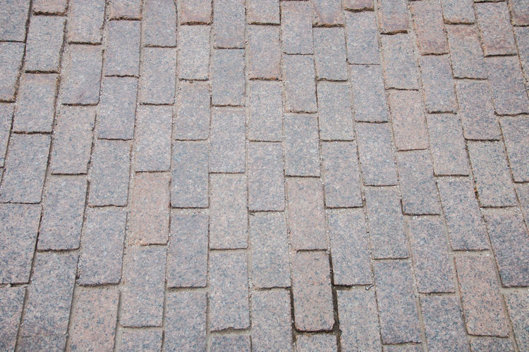 Sand-colored bricks. Stone pavement on the ground for street road. Brick Floor Patio Paving Road Sidewalk Stone Block Construction Material Outdoor Surface Walkway Concrete Garden Laying Pavement Rock Stones Street Way Paver Work Architecture Background Cobble Cobblestone Design Footpath Granite Old Rain Deep Seating Aluminum Roof Brussel Block Job Landscape Grey Black Outside Nobody Abstract Green Armchair Backyard Flowers Pave Pattern Installing Ground