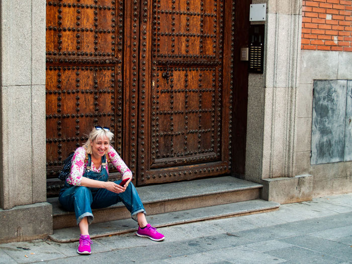 Full length of smiling woman holding mobile phone while sitting at entrance