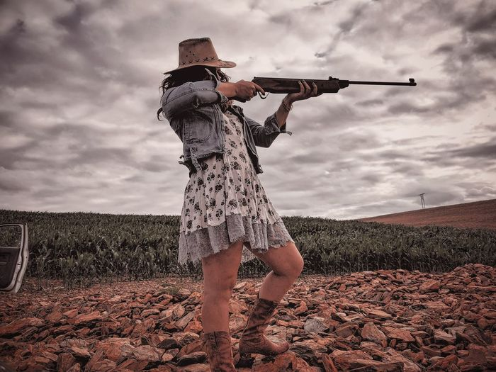 Full length of young woman holding rifle while standing against sky