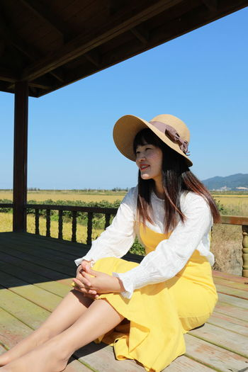 Young woman sitting on railing against clear sky