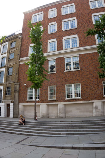 What really catch your eyes first? Red brick building? Stairs? A Tree? or a young lady texting? A Tree Stairs A Young Woman Apartment Architecture Building Building Exterior Built Structure City City Life Day Façade Footpath Full Length Nature Outdoors People Plant Residential District Street Window Young Adult
