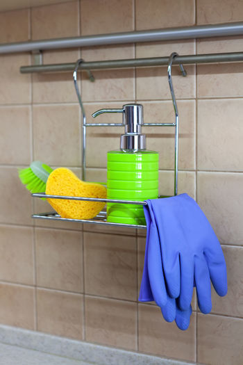 Close-up of gloves and sponge on rack