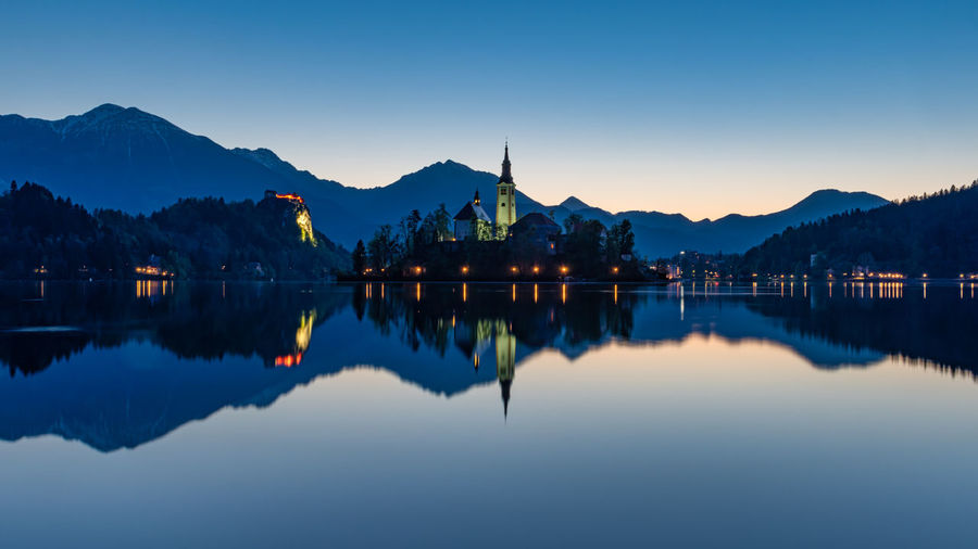 Reflection of church in lake against sky during sunset