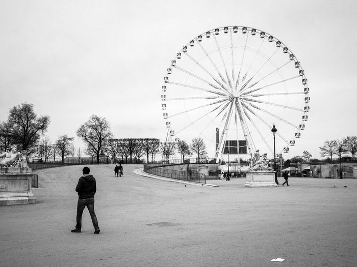 Rear view of man with ferris wheel in city against sky
