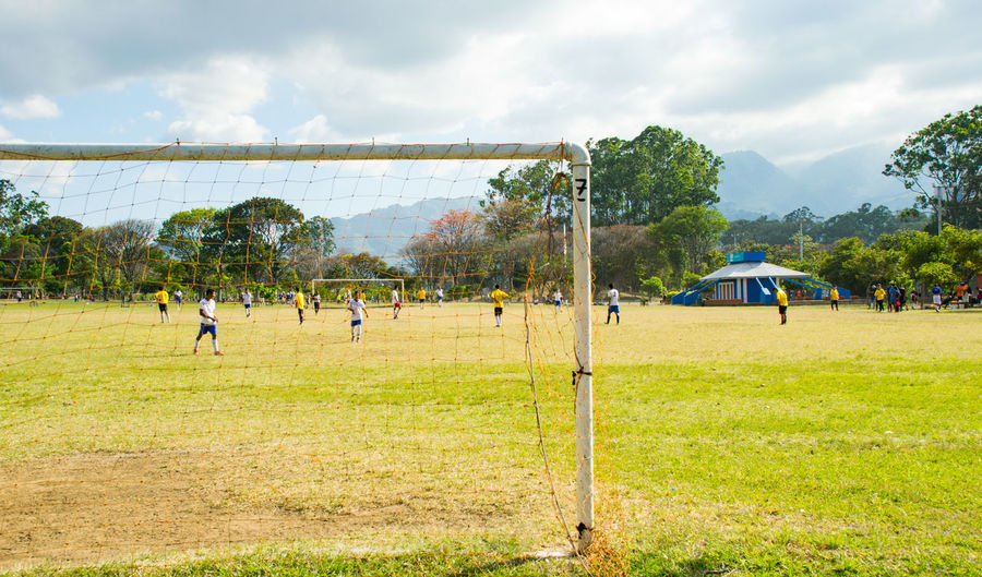 Men playing soccer on field against sky
