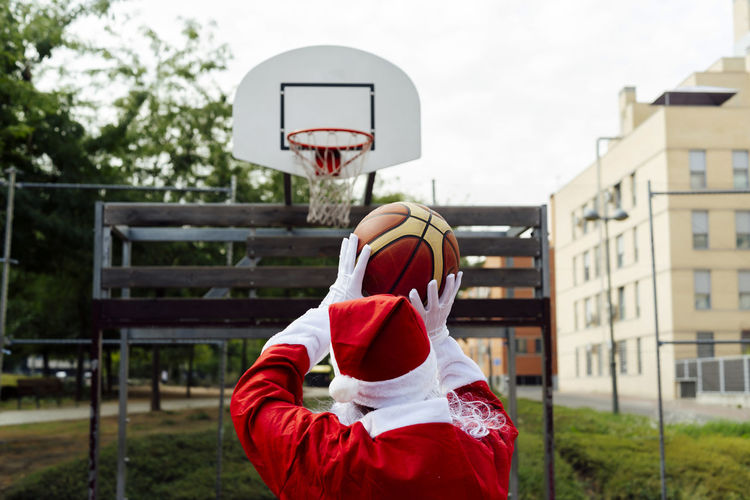 Rear view of person holding basketball hoop