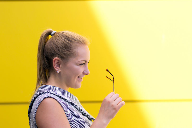Adult Adults Only Blond Hair Close-up Day Headshot Holding Indoors  Microphone Music Musical Note One Person One Young Woman Only People Side View Yellow Yellow Background Young Adult