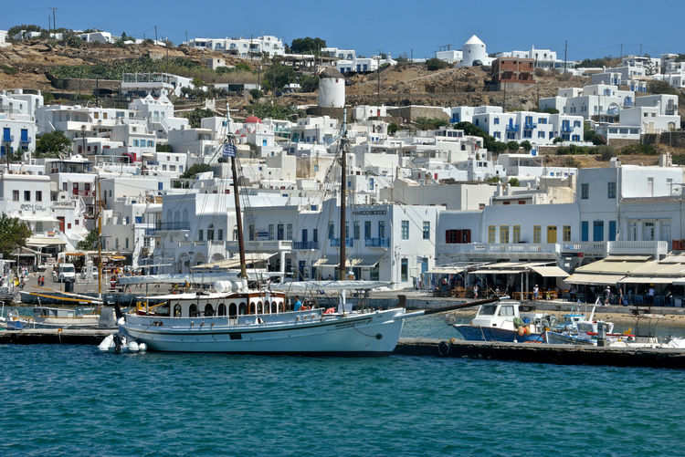 panoramic seaside view of Mykonos with white buildings and harbor with sailing ship moored Building Exterior Nautical Vessel Architecture Transportation Water Built Structure Mode Of Transportation City Residential District Building Nature Sea Day Moored Harbor No People Travel Sunlight Sky Outdoors Sailboat Yacht Cityscape Luxury Yachting Sailing Ship Mykonos,Greece Lifestyles Cruise Cruising Panoramic View Seaside View Greek Architecture Travel Pier Port Maritime Cityscape