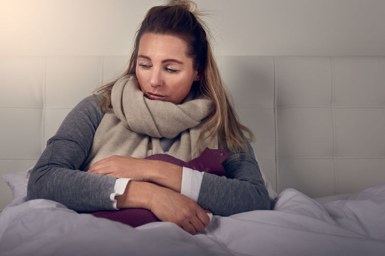 Sick woman with seasonal cold and flu Bed Copy Space Dark Hot Water Bottle Woman Bedroom Best Ager Blond Depressed Evening Face Flu Ill Middle-aged Sad Sadness Sick Sickness Upper Body Woman Portrait